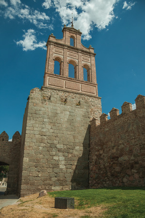 Stone city wall with merlons and tower made by bricks with iron wind vane, in a sunny day at Avila. It has the longest and imposing wall completely encircling this well-kept gothic town in Spain. Imagens