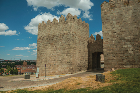 Road going through Carmen Gateway in the stone city wall with towers, in a sunny day at Avila. It has the longest and imposing wall completely encircling this well-kept gothic town in Spain. Imagens