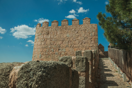 Pathway over old thick wall with battlement and large tower made of stone encircling the town of Avila. It has the longest and imposing wall completely encircling this well-kept gothic town in Spain. Reklamní fotografie