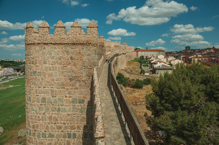 Avila, Spain - July 22, 2018. People on pathway over stone thick wall with large towers encircling Avila. It has the longest and imposing wall completely encircling this well-kept gothic town.