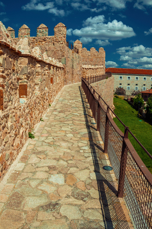 Pathway over old thick wall with battlement made of stone encircling the town of Avila. It has the longest and imposing wall completely encircling this well-kept gothic town in Spain. Retouched photo. Editorial