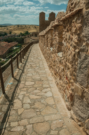 Pathway over old thick wall with battlement and large tower made of stone encircling the town of Avila. It has the longest and imposing wall completely encircling this well-kept gothic town in Spain. Editorial
