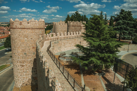 Pathway over old thick wall with battlement and large towers made of stone encircling the town of Avila. It has the longest and imposing wall completely encircling this well-kept gothic town in Spain.