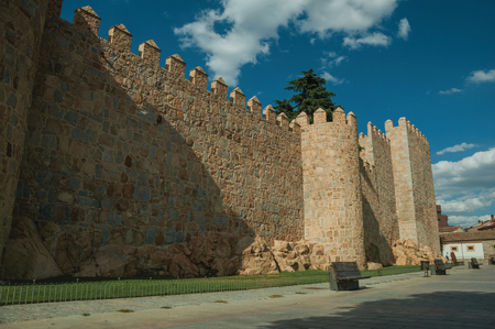 Pedestrian promenade with trees beside large city wall made with rough stones, in a sunny day at Avila. It has the longest and imposing wall completely encircling this well-kept gothic town in Spain.