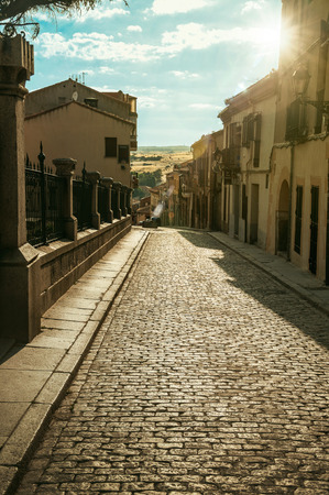 Sunbeam passing through old buildings on an empty alley with stone pavement at Avila. It has the longest and imposing wall completely encircling this well-kept gothic town in Spain. Retouched photo. 스톡 콘텐츠