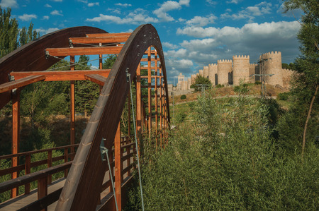 Wooden bridge over the Adaja River with trees and the large wall encircling the town of Avila at sunset. It has the longest and imposing wall completely encircling this well-kept gothic town in Spain.