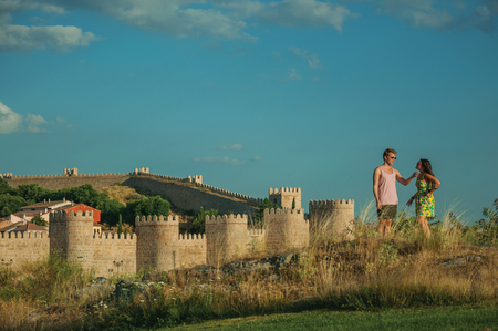 Avila, Spain - July 22, 2018. Couple of lovers over hill and wall with towers around Avila in the background. It has the longest and imposing wall completely encircling this well-kept gothic town. Redakční