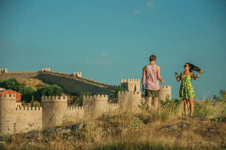 Avila, Spain - July 22, 2018. Couple of lovers over hill and wall with towers around Avila in the background. It has the longest and imposing wall completely encircling this well-kept gothic town. Editorial