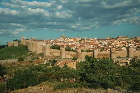 Stone towers with large wall in Romanesque style over the hill, encircling the Avila houses at sunset. It has the longest and imposing wall completely encircling this well-kept gothic town in Spain. Stock Photo