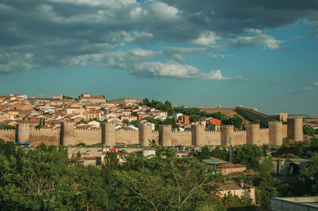 Stone towers with large wall in Romanesque style over the hill, encircling the Avila houses at sunset. It has the longest and imposing wall completely encircling this well-kept gothic town in Spain.
