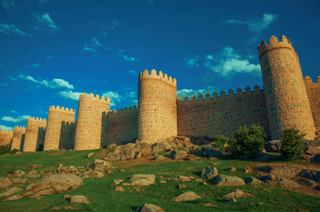 Stone towers in the large wall over rocky terrain, around the town of Avila at sunset. It has the longest and imposing wall completely encircling this well-kept gothic town in Spain. Retouched photo.