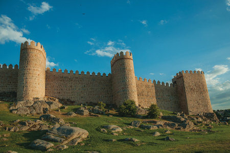 Stone towers in a large wall over rocky landscape with grass, encircling the town of Avila at sunset. It has the longest and imposing wall completely encircling this well-kept gothic town in Spain. Editorial