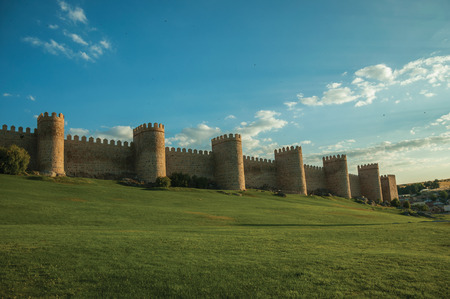 Stone large wall with towers over hilly landscape covered by lawn, encircling the Avila town at sunset. It has the longest and imposing wall completely encircling this well-kept gothic town in Spain. Editorial