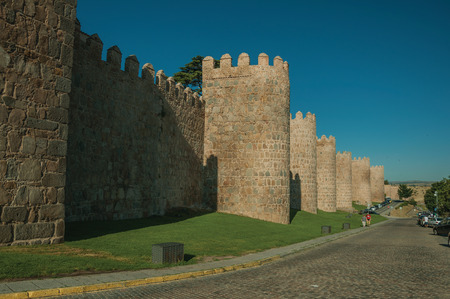 Avila, Spain - July 23, 2018. Stone towers on the city wall in Romanesque style next to street at Avila. It has the longest and imposing wall completely encircling this well-kept gothic town of Spain.
