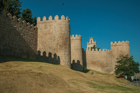 Lined stone towers on the large city wall in Romanesque style and green lawn, in a sunny day at Avila. It has the longest and imposing wall completely encircling this well-kept gothic town of Spain. Redakční