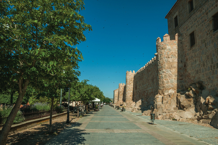 Avila, Spain - July 23, 2018. Pedestrian promenade with trees beside large city wall at Avila. It has the longest and imposing wall completely encircling this well-kept gothic town of Spain.
