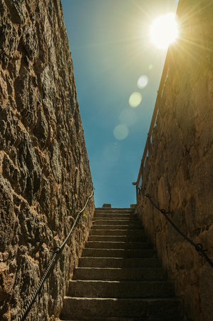 Sunbeam above stone staircase going up towards a thick wall around the town at Avila. It has the longest and imposing wall completely encircling this well-kept gothic town of Spain. Retouched photo.