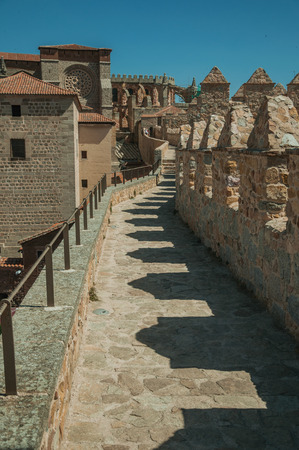 Pathway over thick stone wall with battlement around the town and side view of Cathedral at Avila. It has the longest and imposing wall completely encircling this well-kept gothic town of Spain. Banque d'images