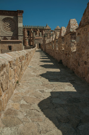 Pathway over thick stone wall with battlement around the town and side view of Cathedral at Avila. It has the longest and imposing wall completely encircling this well-kept gothic town of Spain. Imagens