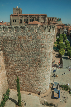 Avila, Spain - July 23, 2018. People walking on street in front of stone tower in wall around Avila. It has the longest and imposing wall completely encircling this well-kept gothic town of Spain.