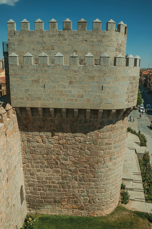 Stone thick wall with large tower encircling the town next to green garden, in a sunny day at Avila. It has the longest and imposing wall completely encircling this well-kept gothic town of Spain.