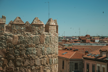 Battlement with merlons and crenels over stone tower and rooftops on buildings, in a sunny day at Avila. It has the longest and imposing wall completely encircling this well-kept gothic town of Spain.