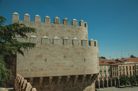 Battlement with merlons and crenels over stone tower and rooftops on buildings, in a sunny day at Avila. It has the longest and imposing wall completely encircling this well-kept gothic town of Spain. Reklamní fotografie