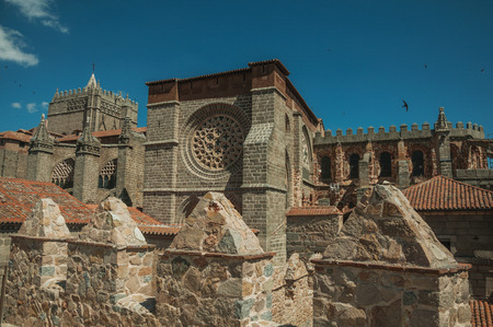 Stone thick wall with battlement and merlons encircling the town next the Cathedral of Avila. It has the longest and imposing wall completely encircling this well-kept gothic town of Spain. Stock Photo