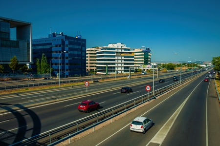 Madrid, Spain - July 23, 2018. Multi lane highway with heavy traffic in a business district in Madrid. Capital of Spain this charming metropolis has vibrant and intense cultural life. Retouched photo. Sajtókép