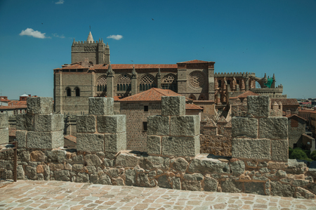 Stone thick wall with battlement and merlons encircling the town next to the Cathedral at Avila. It has the longest and imposing wall completely encircling this well-kept gothic town of Spain. Stock Photo