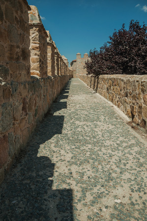 Pathway over thick stone wall with battlement and merlons around the town, in a sunny day at Avila. It has the longest and imposing wall completely encircling this well-kept gothic town of Spain.