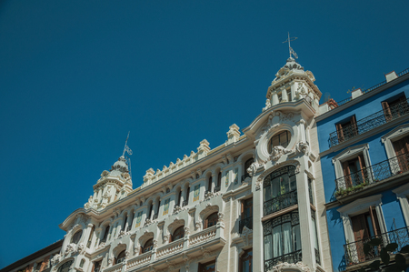 Colorful facade in old charming buildings full of windows and balconies with iron balustrade, on sunny day at Madrid. Capital of Spain this charming metropolis has vibrant and intense cultural life.