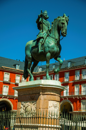 Bronze equestrian statue of King Philip III at the Plaza Mayor square and old buildings in Madrid. Capital of Spain this charming metropolis has vibrant and intense cultural life. Retouched photo.