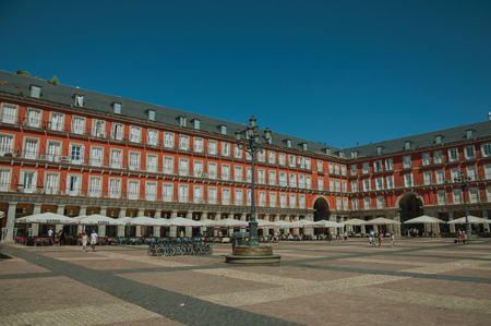 Madrid, Spain - July 24, 2018. People on the Plaza Mayor encircled by old large building with balconies in Madrid. Capital of Spain this charming metropolis has vibrant and intense cultural life.