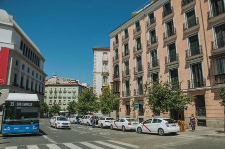 Madrid, Spain - July 24, 2018. Royal Theatre on busy square with people and bus stop, in a sunny day at Madrid. Capital of Spain this charming metropolis has vibrant and intense cultural life. Editorial