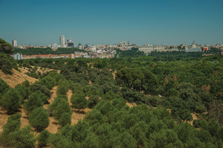 Building skyline on the horizon with green treetops in a sunny day, seen from the Teleferico Park of Madrid. Capital of Spain this charming metropolis has vibrant and intense cultural life. Standard-Bild