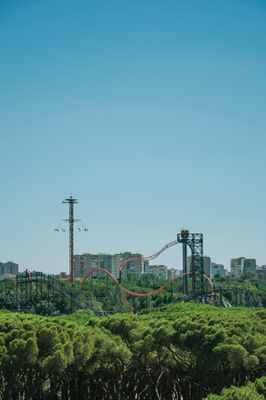 Roller coaster in amusement park on the horizon with trees in a sunny day, seen from the Teleferico Park of Madrid. Capital of Spain this charming metropolis has vibrant and intense cultural life.