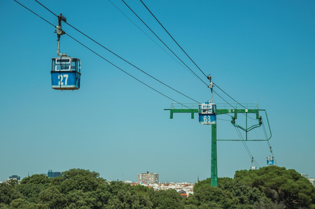Cable car gondola passing through big supporting towers over treetops, in a sunny day at the Teleferico Park of Madrid. Capital of Spain this charming metropolis has vibrant and intense cultural life.