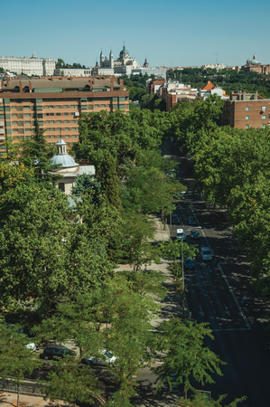 Shaded street with traffic in the midst of garden trees and apartment buildings, in a sunny day at Madrid. Capital of Spain this charming metropolis has vibrant and intense cultural life.