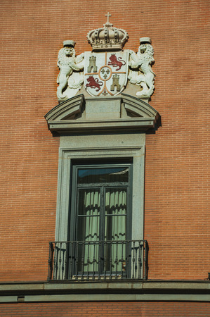 Glazed window with iron balustrade and luxurious carved decoration on bricks facade, in a sunny day at Madrid. Capital of Spain this charming metropolis has vibrant and intense cultural life. Stock Photo