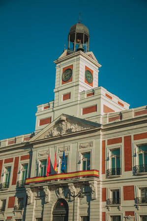 Flags on exquisite old building with plaster decoration and bell tower with clock, in a sunny day at Madrid. Capital of Spain this charming metropolis has vibrant and intense cultural life. Stock Photo