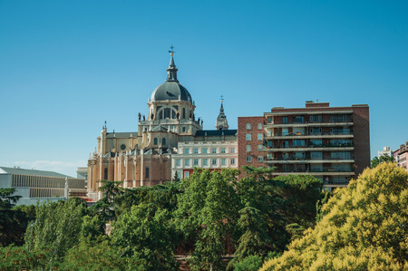 Landscape with the Almudena Cathedral Dome on the horizon amidst green treetops and dwelling, in a sunny day at Madrid. Capital of Spain this charming metropolis has vibrant and intense cultural life.