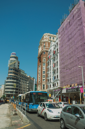 Madrid, Spain - July 25, 2018. Charming old buildings with shops on busy street with people and cars in Madrid. Capital of Spain this charming metropolis has vibrant and intense cultural life.