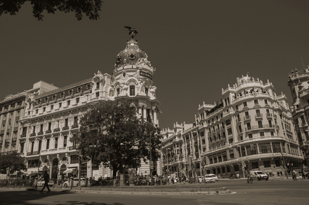 Madrid, Spain - July 25, 2018. Old buildings on the Alcala Street with people and cars in Madrid. Capital of Spain this charming metropolis has vibrant and intense cultural life. Black and white photo Editorial