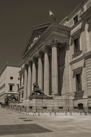 Facade of Palacio de las Cortes, seat of the Congress of Deputies, in a sunny day at Madrid. Capital of Spain this charming metropolis has vibrant and intense cultural life. Black and white photo. Stock fotó