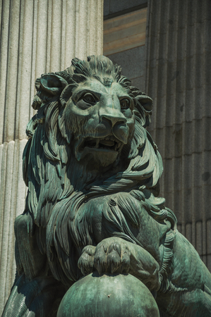 Sculpture of imposing lion cast in bronze on the front facade of Palacio de las Cortes, in a sunny day at Madrid. Capital of Spain this charming metropolis has vibrant and intense cultural life.