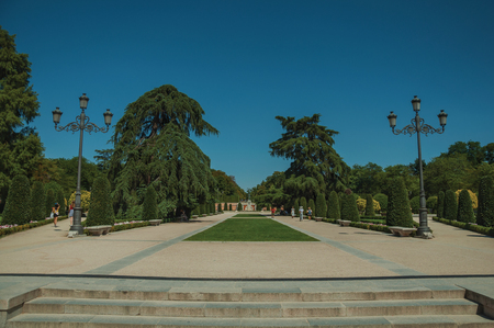 Madrid, Spain - July 25, 2018. Pedestrian promenade with light posts at El Retiro Park, in a sunny day at Madrid. Capital of Spain this charming metropolis has vibrant and intense cultural life. Editorial