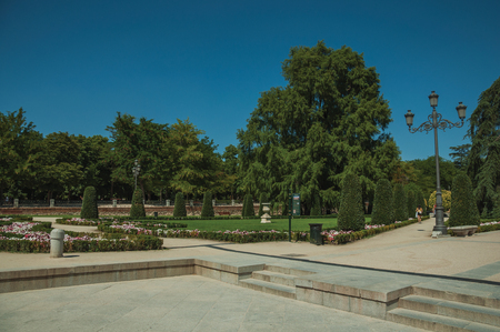 Pedestrian promenade passing through flowered gardens with leafy trees and light posts at El Retiro Park in Madrid. Capital of Spain this charming metropolis has vibrant and intense cultural life.