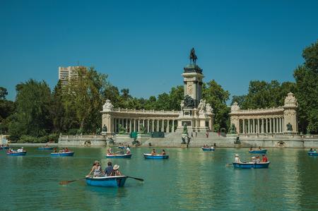 Madrid, Spanien - 25. Juli 2018. Menschen paddeln Boote auf dem reflektierenden Pool und Denkmal im El Retiro Park in Madrid. Hauptstadt von Spanien, diese charmante Metropole hat ein pulsierendes und intensives kulturelles Leben. Editorial