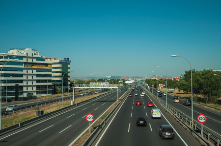 Madrid, Spain - July 25, 2018. Highway with heavy traffic and SPEED LIMIT signposts at business district in Madrid. Capital of Spain this charming metropolis has vibrant and intense cultural life.